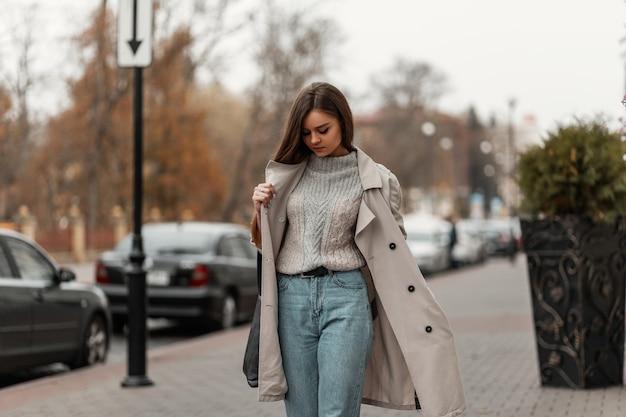 Mulher de cabelos castanhos com roupas de primavera e tênis com uma bolsa de couro posando na rua