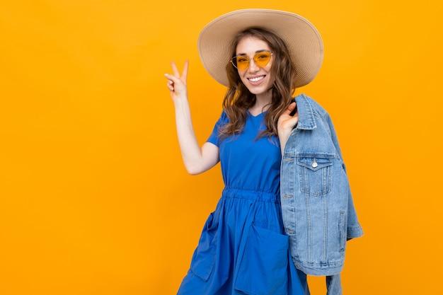 Mulher de cabelos castanhos de meia-idade em uma laranja com um chapéu mostra um sinal de vitória com os dedos
