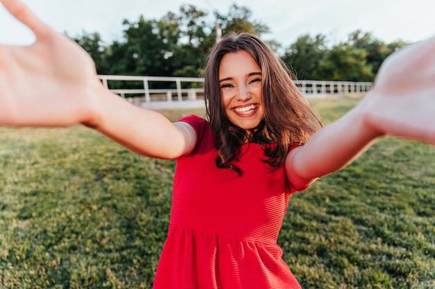 Mulher de cabelos castanhos em êxtase em um traje brilhante, aproveitando o verão. garota incrível de pé na grama e rindo.