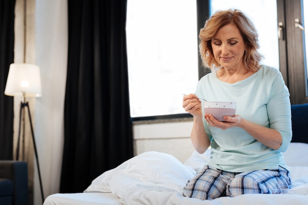 Mulher de cabelos claros. agradável senhora de cabelos curtos sentada na cama com uma tigela de café da manhã leve durante a rotina matinal