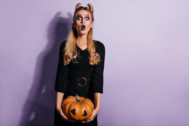 Mulher de cabelos compridos chocada posando após o baile de máscaras de halloween. foto de uma linda menina loira com abóbora.