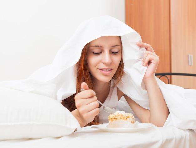 Mulher de cabelos compridos comendo bolo doce sob folha branca na cama