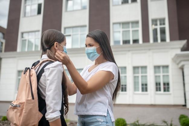 Mulher de cabelos compridos e colegial com mochila e máscara de proteção em pé na frente da escola