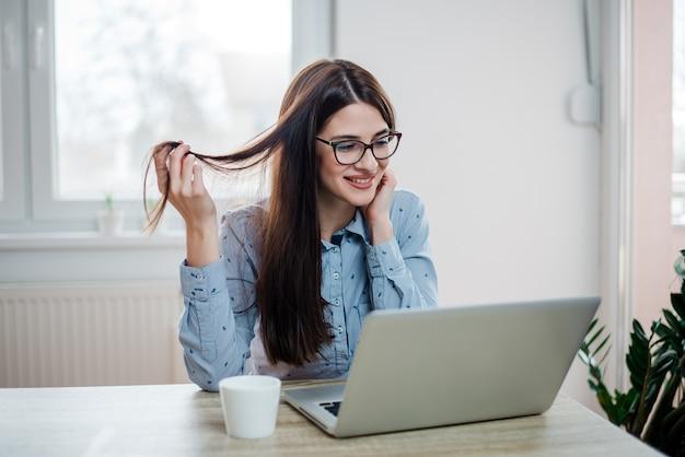 Mulher de cabelos compridos lindo que olha o laptop, em casa.