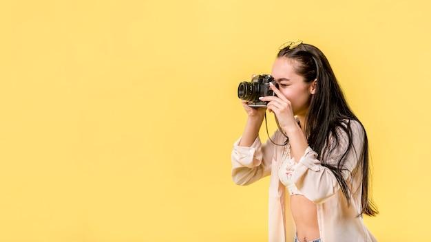 Mulher de cabelos compridos, segurando a câmera fotográfica e tirando foto