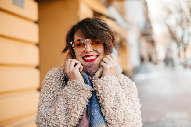 Mulher de cabelos curtos animada caminhando pela cidade