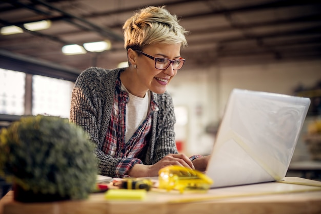 Mulher de cabelos curtos negócios profissional alegre trabalhador escrevendo em um laptop na oficina de tecido