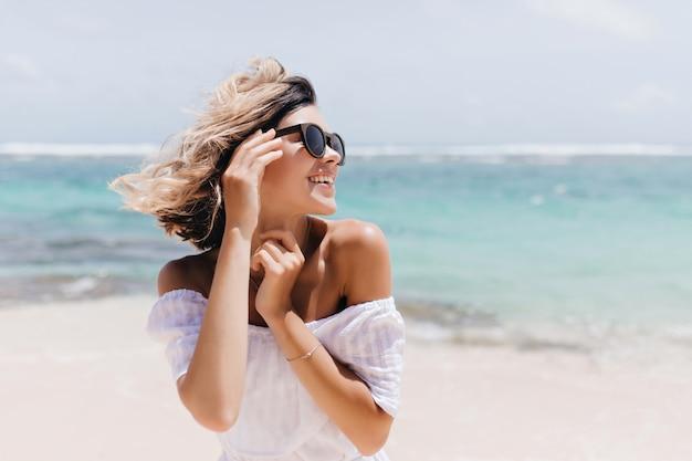 Mulher de cabelos curtos relaxada, posando na praia. foto ao ar livre da alegre jovem em óculos de sol, aproveitando as férias.