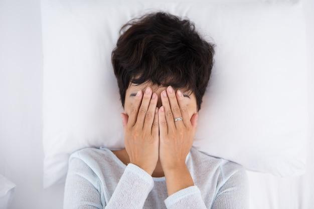 Mulher de cabelos escuros cobrindo rosto e deitado na cama