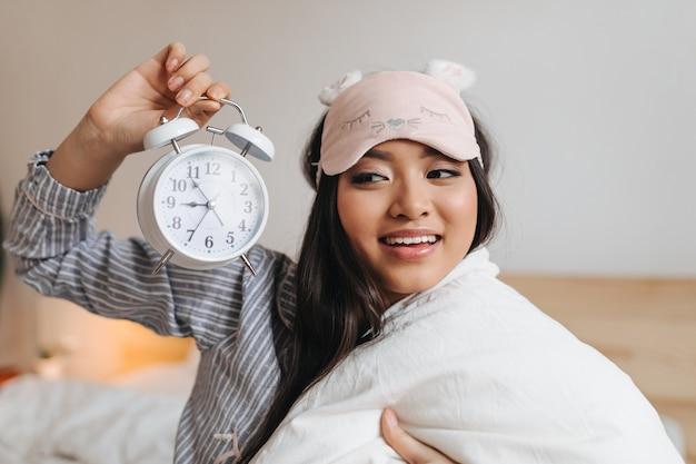 Mulher de cabelos escuros de excelente humor olha para o despertador
