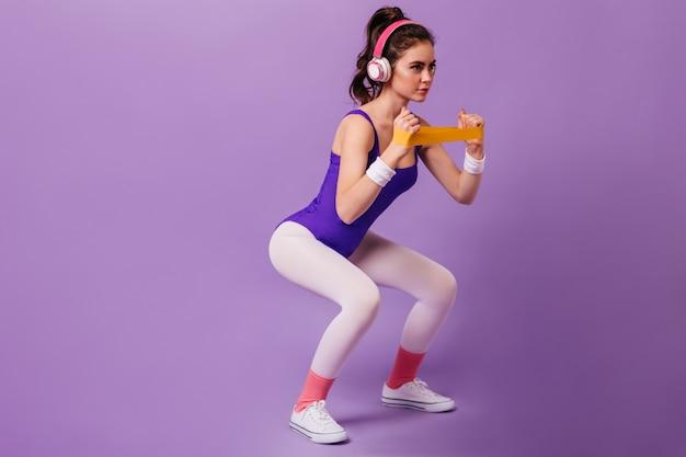 Mulher de cabelos escuros em agasalho de treino roxo e tênis branco agachada com banda para praticar esportes