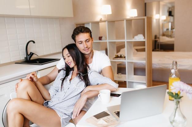 Mulher de cabelos escuros em êxtase em uma camisa azul masculina relaxando com o namorado em um apartamento aconchegante ouvindo música