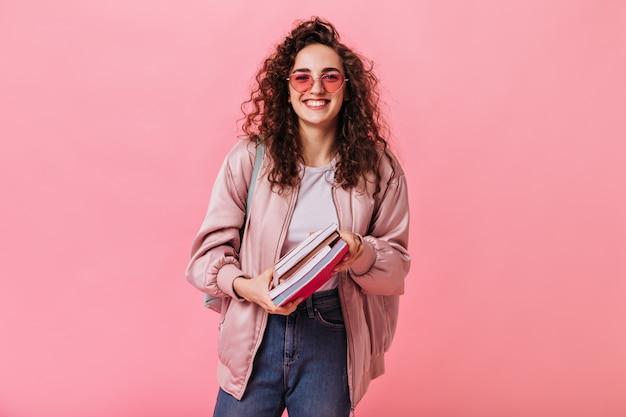 Mulher de cabelos escuros em jeans e jaqueta rosa sorrindo e segurando livros