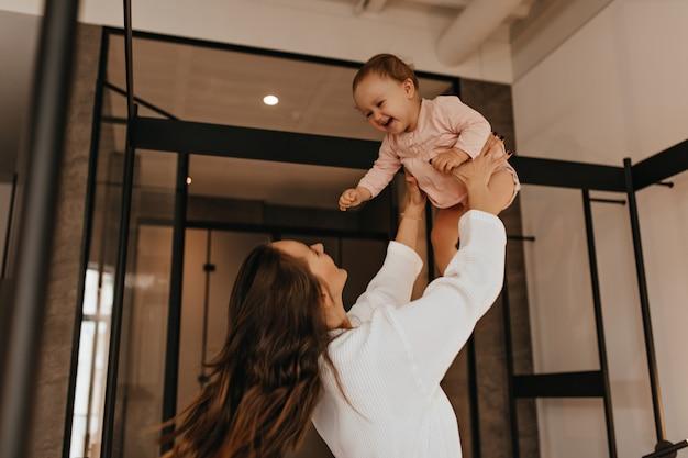 Mulher de cabelos escuros em roupão branco brinca com sua filha e a joga no apartamento.