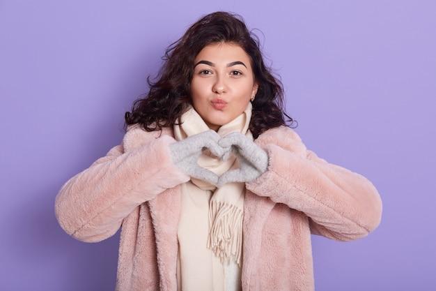 Mulher de cabelos escuros isolada sobre fundo lilás, mostrando um gesto de coração com os dedos