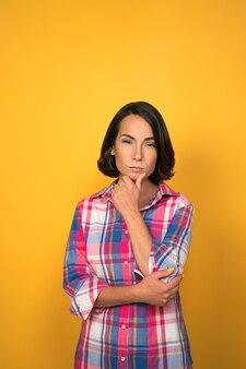 Mulher de cabelos escuros pensativa, olhando para a câmera pensando na ideia. expressões faciais, emoções, sentimentos. mulher com uma camisa xadrez em fundo amarelo.