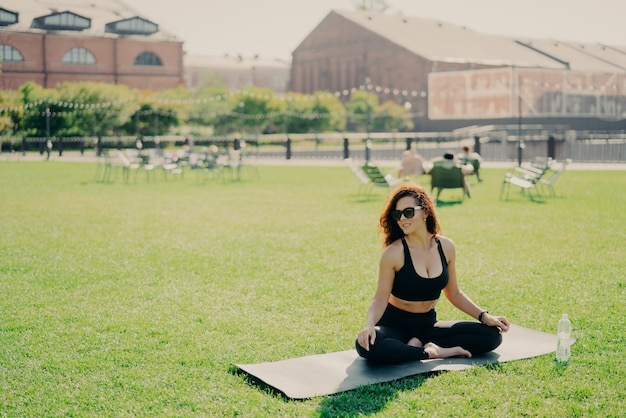 Mulher de cabelos escuros positiva senta-se com as pernas cruzadas com os pés descalços em karemat vestido com roupas esportivas parece alegremente à parte goza de dia ensolarado usa óculos de sol pratica ioga ao ar livre. conceito de estilo de vida esportivo
