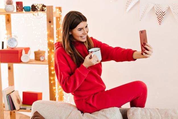 Mulher de cabelos escuros positiva tomando selfie. foto de estúdio de uma jovem atraente bebendo chá.