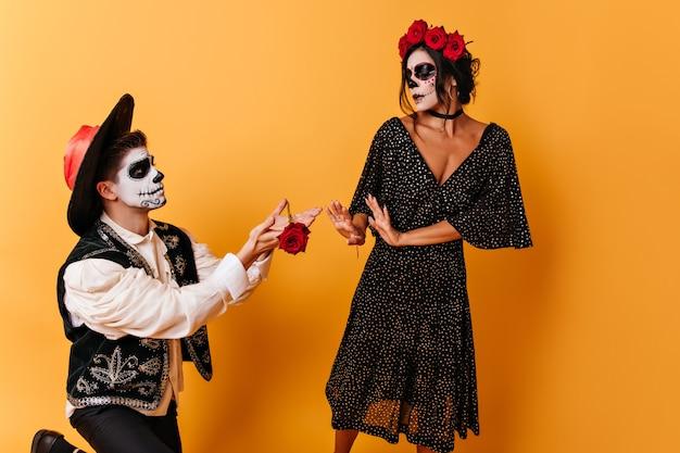 Mulher de cabelos escuros rejeita o presente do menino apaixonado. retrato de corpo inteiro de casal em traje de baile de máscaras.