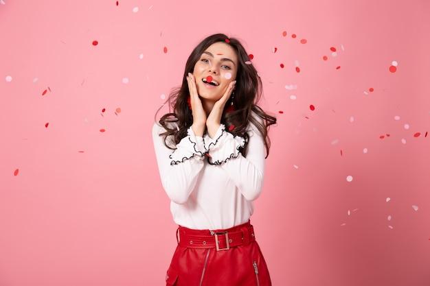 Mulher de cabelos escuros ri no fundo rosa com confete. retrato de jovem com saia vermelha.