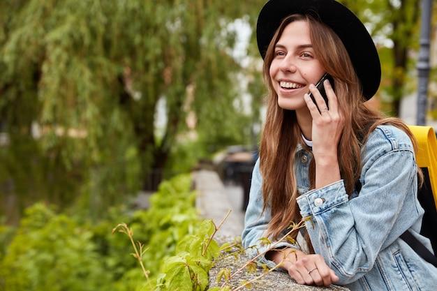 Mulher de cabelos escuros satisfeita falando ao celular no parque da cidade, posa sobre uma árvore verde desfocada, conversa simpática, usa chapéu e jaqueta jeans