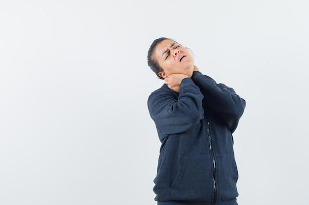 Mulher de cabelos escuros sofrendo de dor no pescoço com a jaqueta e parecendo preocupada