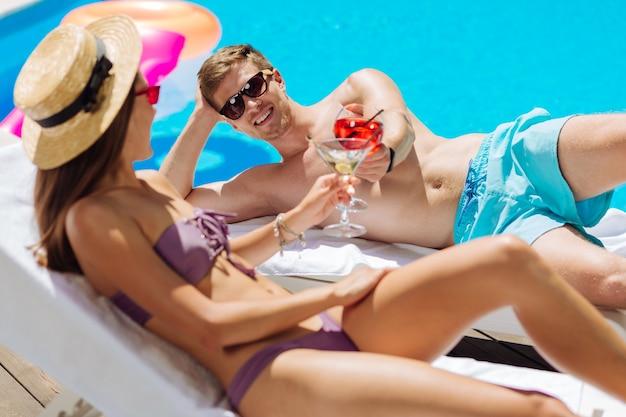 Mulher de cabelos escuros usando um chapéu de palha estiloso tomando banho de sol com seu lindo homem