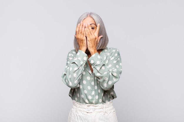 Mulher de cabelos grisalhos cobrindo o rosto com as mãos, espiando por entre os dedos com expressão de surpresa e olhando para o lado