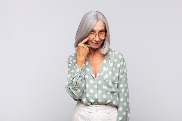Mulher de cabelos grisalhos de olho em você, sem confiar, observando e ficando alerta e vigilante