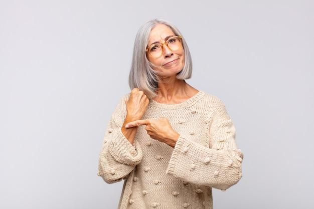 Mulher de cabelos grisalhos impaciente e zangada, apontando para o relógio, pedindo pontualidade, quer ser pontual Foto Premium