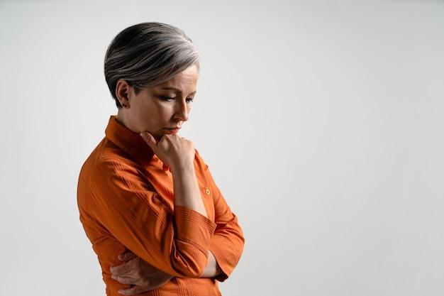 Mulher de cabelos grisalhos madura pensativa em camisa laranja olha para baixo. mulher bonita de cabelos grisalhos em