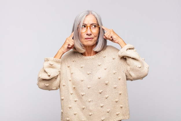 Mulher de cabelos grisalhos olhando concentrada e pensando seriamente em uma ideia, imaginando uma solução para um desafio ou problema