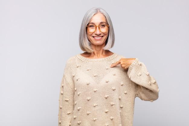 Mulher de cabelos grisalhos parecendo feliz, orgulhosa e surpresa, apontando alegremente para si mesma, sentindo-se confiante e altiva