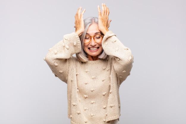 Mulher de cabelos grisalhos se sentindo estressada e ansiosa, deprimida e frustrada com uma dor de cabeça, levantando ambas as mãos à cabeça