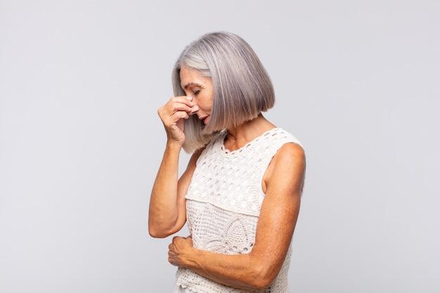 Mulher de cabelos grisalhos se sentindo estressada, infeliz e frustrada, tocando a testa e sofrendo de enxaqueca ou forte dor de cabeça