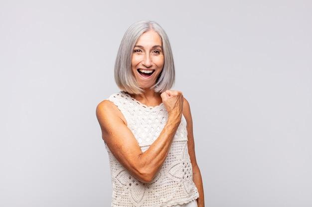 Mulher de cabelos grisalhos se sentindo feliz, positiva e bem-sucedida, motivada para enfrentar um desafio ou comemorar bons resultados