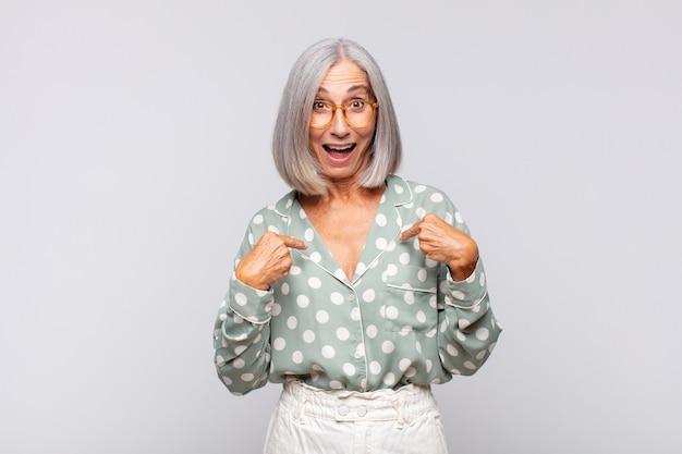 Mulher de cabelos grisalhos se sentindo feliz, surpresa e orgulhosa, apontando para si mesma com um olhar animado e surpreso