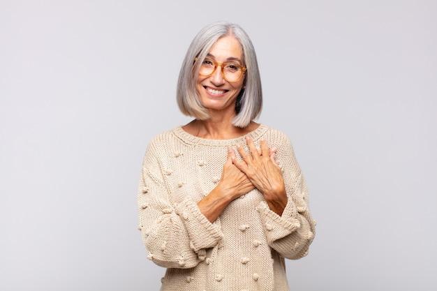 Mulher de cabelos grisalhos se sentindo romântica, sorrindo alegremente e segurando as mãos perto do coração