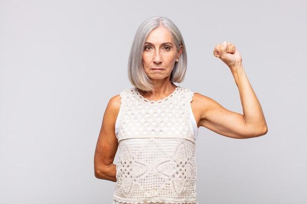 Mulher de cabelos grisalhos se sentindo séria, forte e rebelde, levantando o punho, protestando ou lutando pela revolução