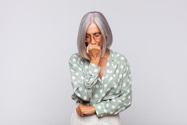 Mulher de cabelos grisalhos se sentindo séria, pensativa e preocupada, olhando de lado com a mão pressionada contra o queixo