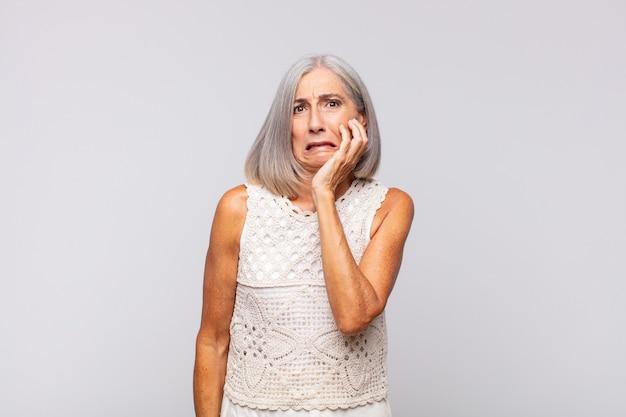 Mulher de cabelos grisalhos segurando a bochecha e sofrendo de uma forte dor de dente, sentindo-se doente, infeliz e infeliz, procurando um dentista