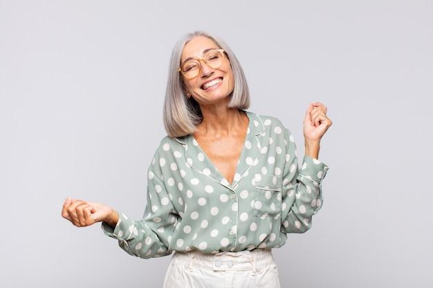 Mulher de cabelos grisalhos sorrindo, sentindo-se despreocupada, relaxada e feliz, dançando e ouvindo música, se divertindo em uma festa