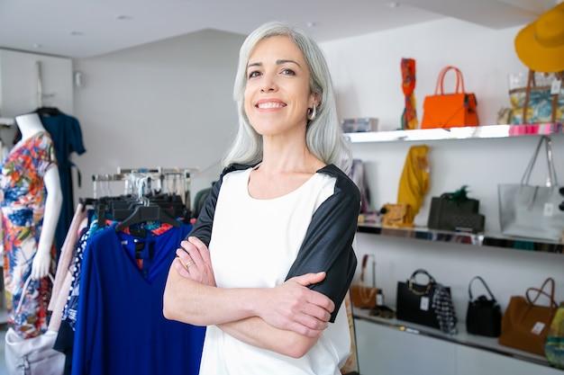 Mulher de cabelos louros caucasiana alegre em pé com os braços cruzados perto do rack com vestidos na loja de roupas, olhando para a câmera e sorrindo. cliente de boutique ou conceito de assistente de loja