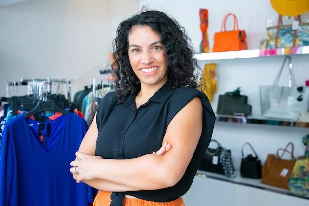 Mulher de cabelos negros latina alegre em pé com os braços cruzados perto da prateleira com vestidos na loja de roupas, olhando para a câmera e sorrindo. cliente de boutique ou conceito de assistente de loja