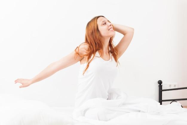 Mulher de cabelos ruivos alegre que acorda na folha branca em sua cama em casa