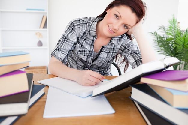 Mulher de cabelos ruivos bem-vinda que estuda em sua mesa