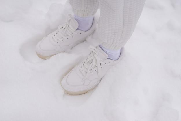 Mulher de calça branca e tênis branco fica em uma neve.