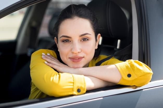 Mulher de camisa amarela, apoiando-se na janela