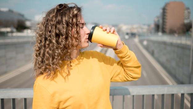 Mulher de camisa amarela, bebendo um café