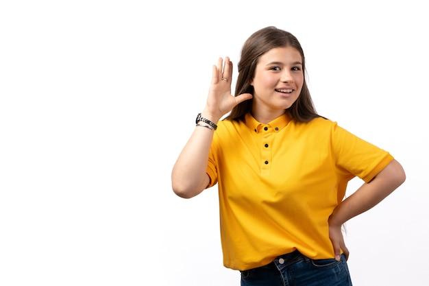 Mulher de camisa amarela e calça jeans posando com uma expressão feliz nas roupas de modelo de mulher de fundo branco